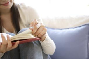 ソファで本を読む30代女性の写真素材 [FYI04037494]