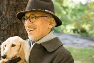 犬を抱いているシニア男性の写真素材 [FYI04037520]