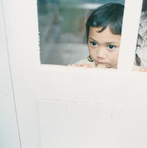 ドアごしにキャンディを食べる女の子の写真素材 [FYI04037586]