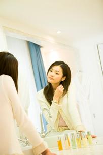 鏡の前に立つ30代女性の写真素材 [FYI04037684]