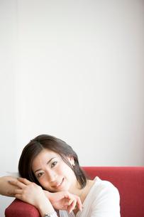 赤いソファに座っている30代女性の写真素材 [FYI04037689]