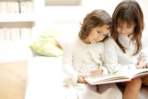 ソファで本を読んでいる姉妹の写真素材 [FYI04037696]