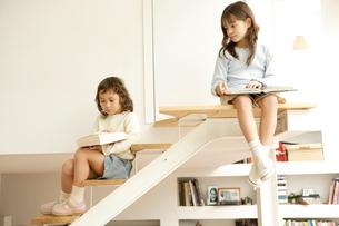 階段で本を読む姉妹の写真素材 [FYI04037711]