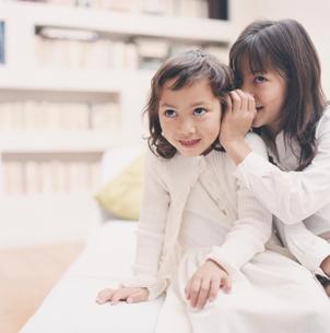 耳打ちをする姉と妹の写真素材 [FYI04037724]