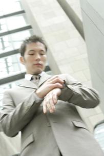 腕時計を見るスーツ姿の30代男性の写真素材 [FYI04037733]