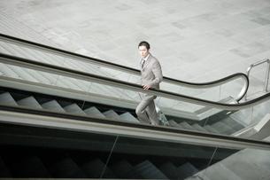 エスカレーターに乗っている30代男性の写真素材 [FYI04037744]