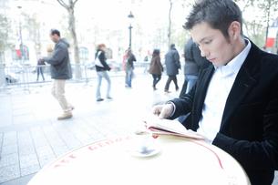 オープンカフェで本を読む30代男性の写真素材 [FYI04037774]