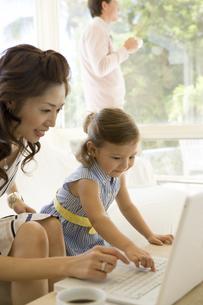 パソコンに向かうお母さんと女の子の写真素材 [FYI04037806]