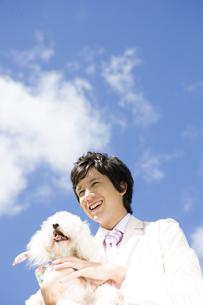 青空と犬を抱いている男性の写真素材 [FYI04037828]