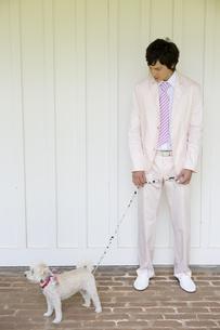 犬とタキシード姿の男性の写真素材 [FYI04037832]