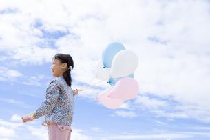 青空と風船を持っている女の子の写真素材 [FYI04037865]