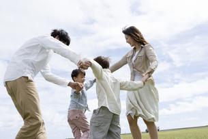 公園で手をつないで回る家族の写真素材 [FYI04037871]