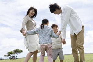 公園で手をつないで回る家族の写真素材 [FYI04037872]