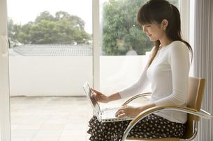 窓辺でパソコンを打つ女性の写真素材 [FYI04037895]