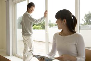 本を読む女性と窓辺に立つ男性の写真素材 [FYI04037896]