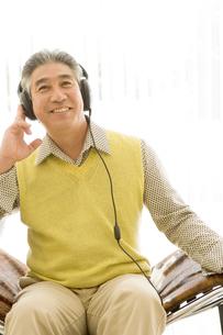 ヘッドフォンで音楽を聴く50代男性の写真素材 [FYI04037923]
