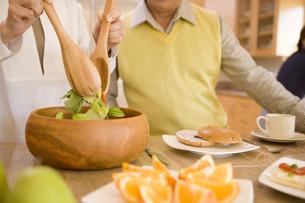 サラダをよそう50代夫婦の手元の写真素材 [FYI04037931]