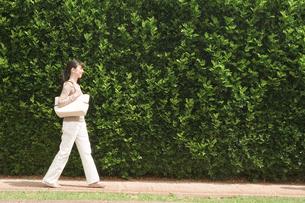 生垣の前を歩く40代女性の写真素材 [FYI04037980]