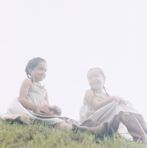 芝生の上に座る双子の女の子の写真素材 [FYI04037988]