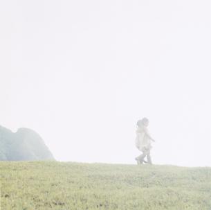 丘を歩く女の子2人の写真素材 [FYI04037989]