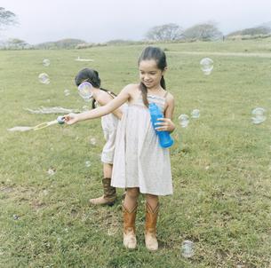 しゃぼん玉で遊ぶ女の子2人の写真素材 [FYI04037991]