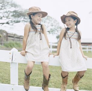 柵に腰掛ける双子の女の子の写真素材 [FYI04037999]