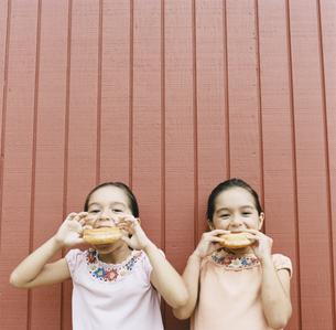 ドーナツを食べる双子の女の子の写真素材 [FYI04038007]
