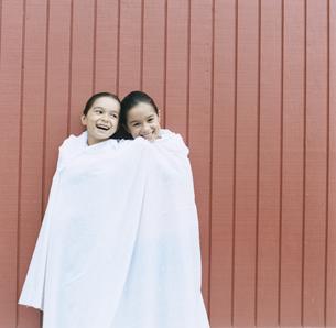 シーツに包まる双子の女の子の写真素材 [FYI04038011]