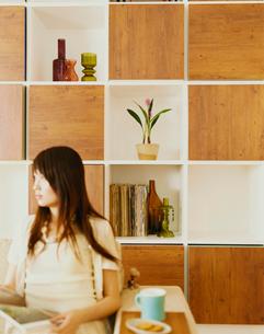 ソファに座って雑誌を読む女性の写真素材 [FYI04038015]