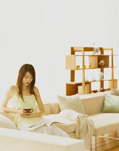 ソファに座って雑誌を読む女性の写真素材 [FYI04038030]