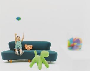 ソファに座る女の子とおもちゃの写真素材 [FYI04038051]
