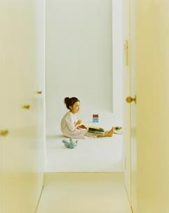 床で本を読む女の子の写真素材 [FYI04038068]