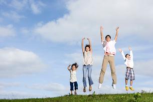 屋外でジャンプする日本人家族の写真素材 [FYI04038154]