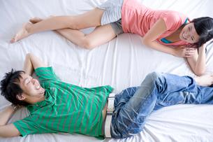寝転ぶ日本人学生カップルの写真素材 [FYI04038216]