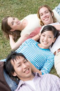 芝生でくつろぐ多国籍学生の写真素材 [FYI04038279]
