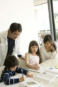 勉強する娘と息子を見る父と母の写真素材 [FYI04038595]