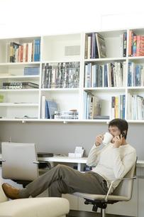 電話をしながらコーヒーを飲む日本人男性の写真素材 [FYI04038658]