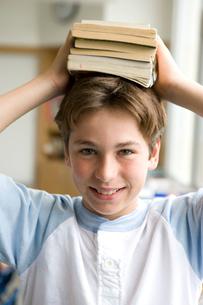 頭に本を載せた笑顔の男の子の写真素材 [FYI04038685]
