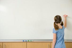 ホワイトボードに文字を書く女の子の後ろ姿の写真素材 [FYI04038727]