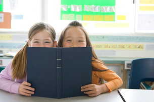本で顔を隠す笑顔の女の子二人の写真素材 [FYI04038732]