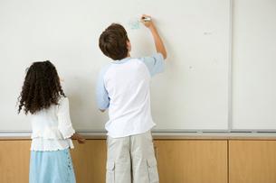 ホワイトボードに文字を書く男の子と女の子の写真素材 [FYI04038738]