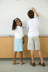 ホワイトボードに文字を書く男の子と女の子の写真素材 [FYI04038740]