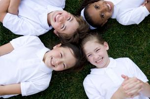 グラウンドに笑顔で寝転ぶ子供達の写真素材 [FYI04038779]