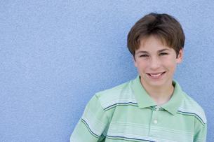 青い壁の前で微笑む男の子のポートレートの写真素材 [FYI04038801]