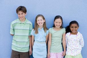 青い壁の前で微笑む子供たちのポートレートの写真素材 [FYI04038804]