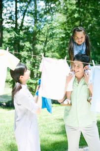 洗濯物を干す母と父と娘の写真素材 [FYI04038851]