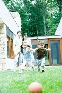 庭で遊ぶ子供と夫婦の写真素材 [FYI04038862]