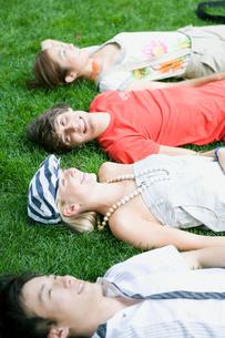 芝生に寝転がる学生達の写真素材 [FYI04038981]