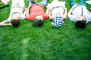 芝生に寝転がる学生達の写真素材 [FYI04038984]