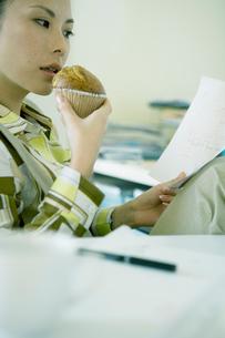 マフィンを食べながら仕事する女性の写真素材 [FYI04039043]